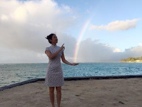 woman holding rainbow on Hawaii beach
